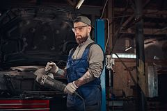 Brutal auto mechanic in a uniform and safety glasses working with an angle grinder while standing against a broken car. In the repair garage Royalty Free Stock Image