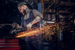 Brutal auto mechanic in a uniform and safety glasses working with an angle grinder while standing against a broken car. In the repair garage Stock Photos