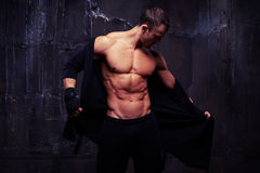 Brutal bare-chested muscular male taking off a black hoodie whil Stock Photos