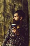 Brutal bearded hipster holding plastic coffee cup. Brutal caucasian bearded hipster with moustache holding plastic coffee cup or mug on wooden background in stock images