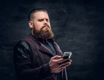 Bearded  male texting an SMS on a smartphone. Brutal bearded hipster male texting an SMS on a smartphone Royalty Free Stock Photography