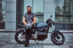 Brutal bearded male in a gray t-shirt and black pants holds a helmet sitting on his custom-made retro motorcycle against royalty free stock photography