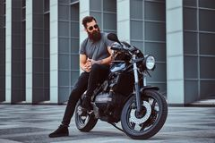 Brutal bearded male in sunglasses dressed in a gray t-shirt and black pants sitting on his custom-made retro motorcycle. Against skyscraper Royalty Free Stock Photography