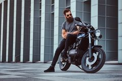 Brutal bearded male in sunglasses dressed in a gray t-shirt and black pants sitting on his custom-made retro motorcycle. Against skyscraper Stock Photo