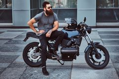 Brutal bearded male in sunglasses dressed in a gray t-shirt and black pants sitting on his custom-made retro motorcycle. Against skyscraper Royalty Free Stock Photo