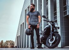 Brutal bearded male in sunglasses dressed in a gray t-shirt and black pants standing near his custom-made retro. Motorcycle against a skyscraper Royalty Free Stock Photo