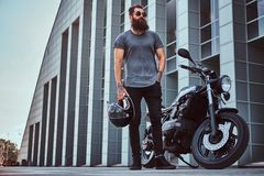 Brutal bearded male in sunglasses dressed in a gray t-shirt and black pants standing near his custom-made retro. Motorcycle against a skyscraper Royalty Free Stock Images