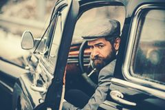 Brutal bearded man with a smart mustache brunette sitting in a saloon car retro. stock photography