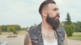 A brutal bearded man with tattoos walks through the city with a black bag. A brutal bearded man with tattoos walks through the city with a black bag royalty free stock image