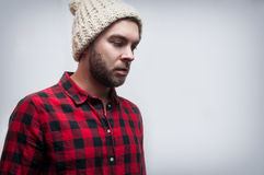 Brutal bearded man wearing knitted cap and plaid shirt Stock Image