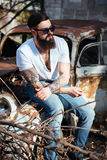 Brutal bearded man with tattoo in jeans clothes is sitting on the hood of the old car Stock Photos
