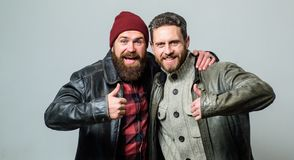 Brutal bearded men wear leather jackets. Real men and brotherhood. Friends glad see each other. Friendly relations. Friendship of brutal guys. Real friendship stock image