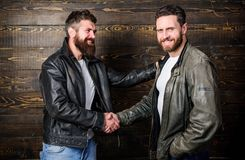 Brutal bearded men wear leather jackets shaking hands. Real men and brotherhood. Strong handshake. Friendship of brutal. Guys. Mafia dealer. Real friendship of stock photo