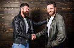 Brutal bearded men wear leather jackets shaking hands. Real men and brotherhood. Strong handshake. Friendship of brutal. Guys. Mafia dealer. Real friendship of stock photo
