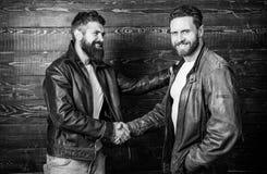 Brutal bearded men wear leather jackets shaking hands. Real men and brotherhood. Strong handshake. Friendship of brutal. Guys. Mafia dealer. Real friendship of stock image