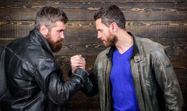 Brutal bearded men wear leather jackets shaking hands. Strong handshake. Friendship of brutal guys. Handshake symbol of. Successful deal. Approved business deal royalty free stock images