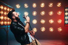 Brutal bearded singer with microphone on the stage. With the decorations of lights Royalty Free Stock Photo