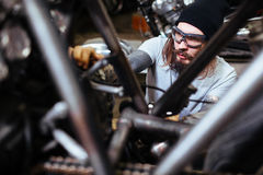 Brutal Biker Assembling Motorcycle in Garage. Portrait of tattooed man working in garage customizing motorcycle and tuning it up stock photo