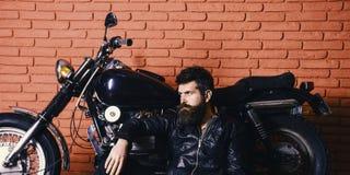 Brutal biker concept. Hipster, brutal biker on pensive face in leather jacket sit on floor near motorcycle. Man with. Beard, biker in leather jacket near motor Stock Image