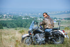 Brutal biker sitting on his motorcycle on a sunny day Royalty Free Stock Photo