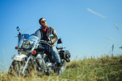 Brutal biker sitting on his motorcycle on a sunny day Stock Photo