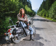 Brutal biker sitting on his motorcycle on a sunny day Stock Images
