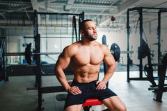 Brutal bodybuilder next to barbells. Young sports man with six pack abs on a gym background. Active lifestyle concept. Stock Photos