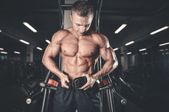 Brutal bodybuilder powerful training arms, pectorals and shoulde Stock Photo