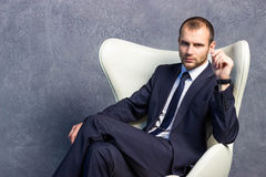 Brutal businessmen in suit with tie sitting on chair Stock Photos