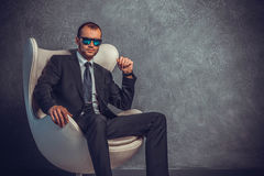 Brutal businessmen in suit with tie and sunglasses sitting on chair Royalty Free Stock Image