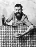 Brutal caucasian hipster holding tropical alcohol fresh cocktail. Bearded man, long beard. Brutal caucasian tattooed hipster with moustache in denim shirt stock image