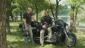 Brutal male bikers chatting about motorbike outdoors stock video