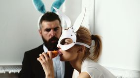 Brutal couple in a leather mask gnawing carrot like a rabbits. Backgrounde. Isolated in white. Funny couple. Passionate. Couple in masks. Carrot in her mouth stock video footage