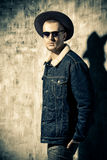 Brutal denim style. Stylish brutal man wearing jeans clothes and sunglasses posing over grunge background. Denim collection. Male fashion Royalty Free Stock Photos