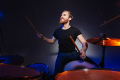 Brutal excited young man drummer with beard playing drums Royalty Free Stock Images