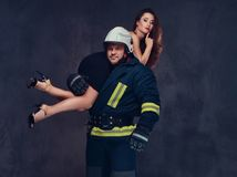 Firefighter holds a woman. Brutal firefighter holds sexy and hot brunette female dressed in a black dress on his shoulder Royalty Free Stock Photos
