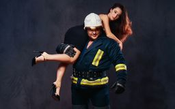 Firefighter holds a woman. Brutal firefighter holds sexy and hot brunette female dressed in a black dress on his shoulder Stock Photo