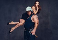Firefighter holds a woman. Brutal firefighter holds and hot brunette female on his shoulder royalty free stock image