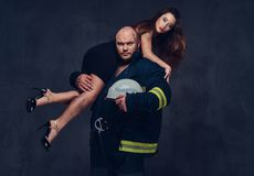 Firefighter holds a woman. Brutal firefighter holds sexy and hot brunette female on his shoulder Stock Photos