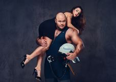 Firefighter holds a woman. Brutal firefighter holds and hot brunette female on his shoulder royalty free stock photography