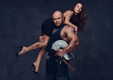 Firefighter holds a woman. Brutal firefighter holds sexy and hot brunette female on his shoulder Stock Photography