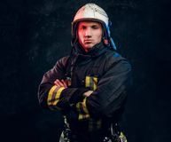 Brutal fireman in uniform posing for the camera standing with crossed arms and confident look. stock image