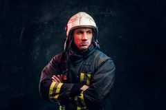 Brutal fireman in uniform posing for the camera standing with crossed arms and confident look. royalty free stock photography