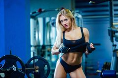 Brutal fitness woman with a muscular in the gym. Sports and fitness - concept of healthy lifestyle. Fitness woman stock photos