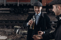 Brutal gangsters drinking on background of railway carriage. en. Gland in 1920s theme. fashionable confident man. atmospheric moments. space for text. peaky royalty free stock image