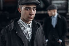 Brutal gangsters posing on background of railway carriage. engla Stock Photos