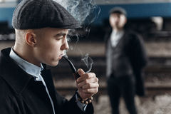 Brutal gangsters smoking and posing on background of railway. en Stock Images