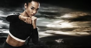 A strong athletic, woman boxer, boxing at training on the sky background. Sport boxing Concept with copy space. Brutal girl boxer ready for battle in the Royalty Free Stock Photography
