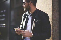 Brutal guy in a leather jacket and sunglasses. Young handsome man traveler using smartphone application to find right direction in the city, trendy hipster guy Stock Photos