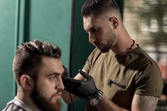 Brutal handsome man with beard sits at a barber shop. Barber makes a trim at the side. stock photos